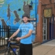 Jesse Descutner, assistant Main Street manager for the Northside Leadership Conference, stops on Foreland Street in Deutschtown near Allegheny City Brewery, on of 14 businesses participating in the We Like Bikes! initiative. (Nate Guidry/Post Gazette)